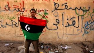 A Libyan anti-government protester holds his old national flag in front of a wall covered with graffiti against Libyan leader Muammar Gaddafi in the eastern city of Tobruk on February 24, 2011