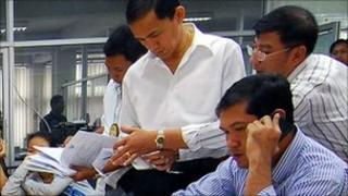 Thai police talk to the Vietnamese women at the Immigration Police Bureau in Bangkok on 24 February 2011