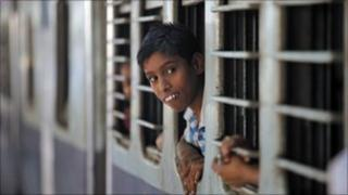 Boy looking out of a train in Kolkata train station