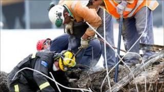 Rescue workers search through the CTV building site