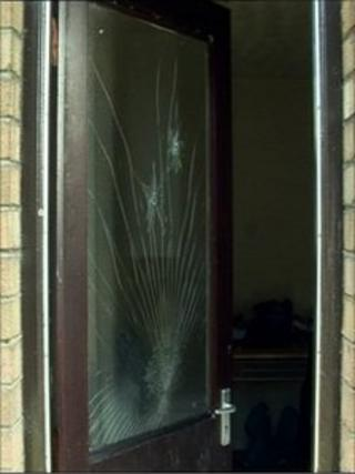 Door with two bullet holes in the glass