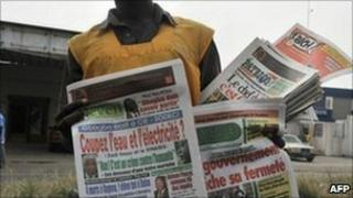 A street vendor sells newspapers in Abidjan. Photo: January 2011