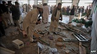 Pakistani security personnel investigate the bomb blast site in Nowshera on March 4, 2011.