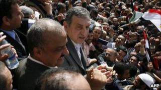 Egyptian Prime Minister- designate Essam Sharaf, with microphone, speaks to demonstrators at Tahrir Square in Cairo, Egypt