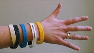 Hand with a selection of wrist bands in aid of charitable events