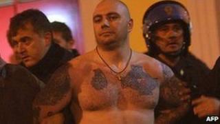 Italian police escort Ivan Bogdanov after the Genoa match, 13 October
