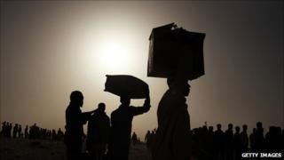 Men who recently crossed into Tunisia from Libya carry their bags at a UN displacement camp on 7 March 2011 in Ras Jdir, Tunisia