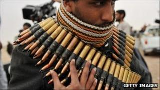 Rebel wrapped up in machine gun ammunition on the road from Ras Lanuf, Libya