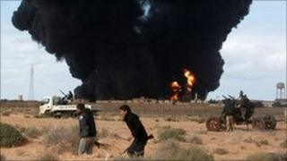Rebels walk past a burning oil terminal hit by pro-Gaddafi forces near Ras Lanuf, 9 March