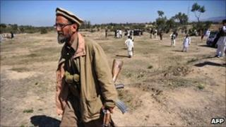 An armed Pakistani anti-Taliban militia member walks at a suicide blast site in the village of Adezai, near Peshawar on March 9, 2011