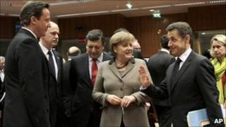 From left, British Prime Minister David Cameron, Greek Prime Minister George Papandreou, European Commission President Jose Manuel Barroso, German Chancellor Angela Merkel and French President Nicolas Sarkozy share a word at an EU Summit in Brussels on 11 March 2011