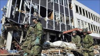 Japanese soldiers walk past a damaged building in the city of Rikuzentakada, Japan, on 12 March, 2011