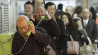 Stranded people stand in a line to use public telephones at a train station after subway and train services were suspended after an earthquake, in Tokyo March 11, 2011.