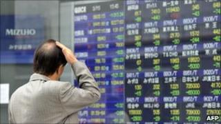 A investor gazes at a share prices board in Tokyo