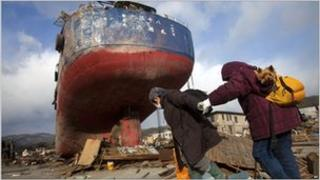 Two elderly woman pass a beached ship in the tsunami-hit town of Kesennuma on 17 March 2011
