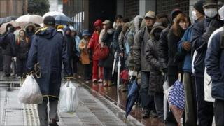 People queuing outside a shop in Japan