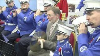 Nelson McCausland and a marching band
