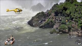 A helicopter and boat search the water at the foot of Iguazu Falls