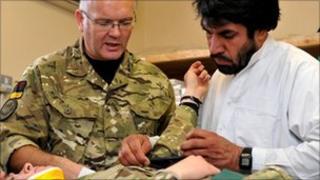 Captain Robert Garbett training an Afghan nurse