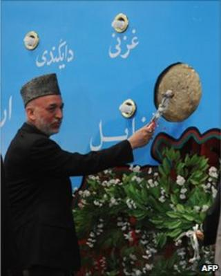 Afghan President Hamid Karzai rings a school bell during a ceremony held to mark the start of the new educational year at The Amani High School in Kabul on March 23, 2011.