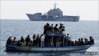 Migrants from Tunisia on a boat in front of Italian navy ship San Marco (23 March 2011)
