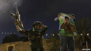A soldier from the Libyan army loyal to Libya's leader Muammar Gaddafi fire shots in the air in Tripoli March 20, 2011