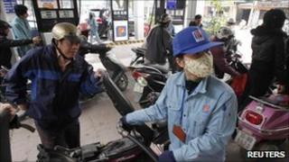 A customer pumps petrol to a motorcycle at a gas station in Hanoi