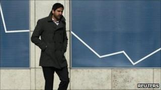 A man passes an advertisement in the Canary Wharf financial district in London, 16 February 2011