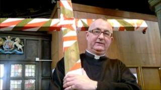 Father Needham, holding a large wooden crucifix