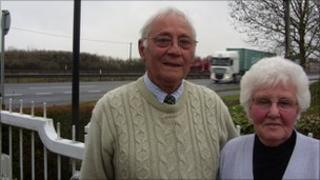John and Grace Willis in their front garden alongside the A12