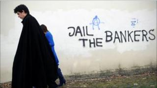Student in traditional garb passes anti-capitalist graffiti in Coimbra, Portugal