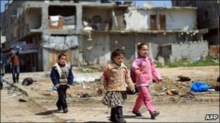 Children walk past a destroyed building in Gaza City