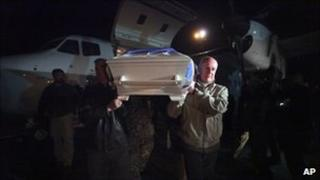 The head of the UN Assistance Mission in Afghanistan (Unama), Staffan de Mistura, carries the coffin of a UN staff member killed in the attack in Mazar-e Sharif from a jet a Kabul airport (2 April 2011)