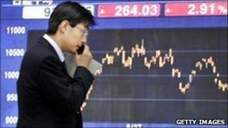 A businessman uses his mobile phone before a share prices board