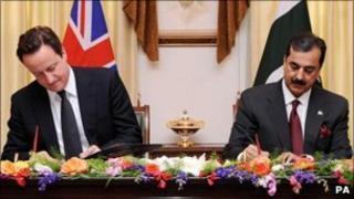 David Cameron signs a document with Pakistan PM Yousuf Raza Gilani