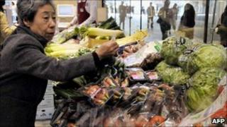 A shopper looks at vegetables for sale in Japan on 6 April 2011