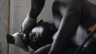 A patient wounded in Abidjan in March 2011 is attendd to by a nurse