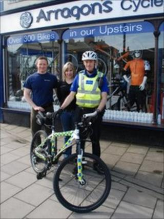 PCSO Tony Labram with Phil and Sarah Graham of Arragon's Cycles and one of the new bicycles