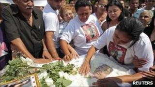 The mother of one of the victims of the Rio school shooting Luiza Paula da Silveira, touches her coffin during her funeral in Realengo cemetery