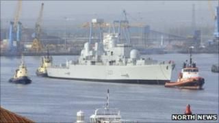 HMS Bristol being guided out of the Tyne