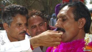 Released Indian national Gopal Das wearing garlands receives sweets from his relative after crossing into India