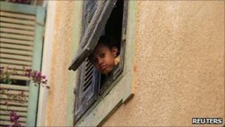 A Libyan child looks out of the window in Tripoli, 6 April 2011