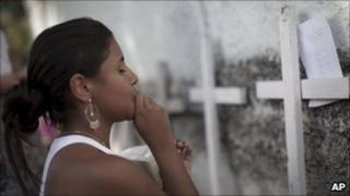 A girl kneels in prayer at a makeshift memorial for victims of a school gun attack in Rio de Janeiro, Brazil, 9 April 2011