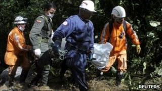 Rescue workers carry a victim of the bus accident on the Manizales-Bogota road in Colombia