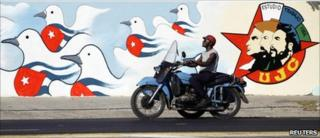 A man rides his motorcycle past a freshly painted mural by the Union of Young Communists, in Havana April 15, 2011