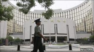 Guard walks past the People's Bank of China in Beijing