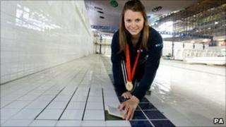 Liz Johnson laying the final tile in the Olympic pool