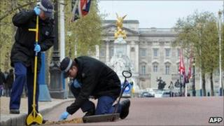 Police officer checking drain in front of Buckingham Palace