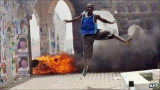 A man jumps during a demonstration in Nigeria's northern city of Kano where running battles broke out between protesters and soldiers on 18 April 2011