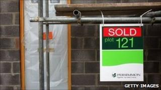 """Home under construction with Persimmon """"sold"""" sign in front"""